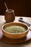 Mate Tea. South American yerba mate (mate tea) dried leaves in wooden bowl with a wooden mate cup and strainer (bombilla) in the back, photographed with natural royalty free stock photo