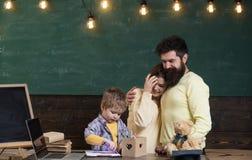 Mateczny poparcia pojęcie Rodzice ogląda ich syna rysunek, uczenie pisać na tle, chalkboard Chłopiec na ruchliwie Fotografia Stock