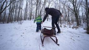 Mateczny poparcie, ojciec pomocy syna wspinaczki śnieżna góra z saniami w rękach przy zimą zdjęcie wideo