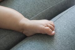Matek ręki i dziecko cieki na szarej kanapie zdjęcia royalty free