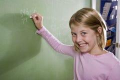Matemáticas feliz de la escritura de la muchacha en la pizarra en clase Imágenes de archivo libres de regalías
