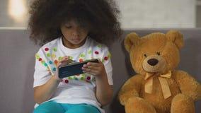 Matemáticas practicante del niño femenino afroamericano en el smartphone, apps educativos metrajes