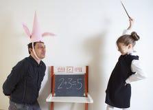 Matematica d'istruzione della bambina ad un dunce adulto fotografia stock libera da diritti
