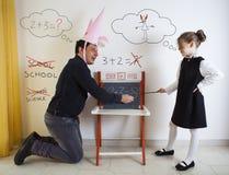 Matematica d'istruzione della bambina ad un dunce adulto fotografie stock