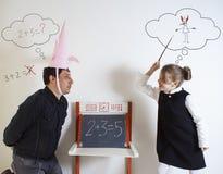 Matematica d'istruzione della bambina ad un dunce adulto fotografia stock