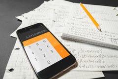 Matematiska likställande som är skriftliga i en anteckningsbok Räknemaskin app Royaltyfria Bilder