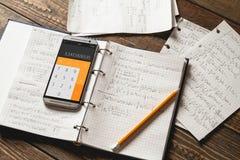 Matematiska likställande som är skriftliga i en anteckningsbok Räknemaskin app Royaltyfri Bild