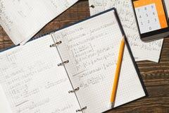 Matematiska likställande som är skriftliga i en anteckningsbok Räknemaskin app Arkivfoto
