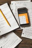 Matematiska likställande som är skriftliga i en anteckningsbok Räknemaskin app Royaltyfri Foto