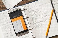 Matematiska likställande som är skriftliga i en anteckningsbok Räknemaskin app Arkivfoton