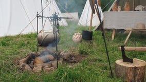 Maten lagas mat på insatsen i lergods enligt gamla traditioner Tält för läger för gräs för journal för yxaträdjournal wood lager videofilmer