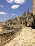 Matera Road to Cathedral. View of the Cathedral and winding roads and ancient prehistoric ruins in the cave village of Matera, Italy stock images