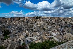 Wide panoramic cityscape view of Matera, Italy. MATERA, ITALY - AUGUST 27, 2018: High angle summer day panoramic view over Church of Saint Peter or Chiesa di San royalty free stock photography