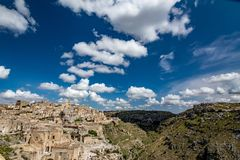 Wide panoramic cityscape view of Matera, Italy. MATERA, ITALY - AUGUST 27, 2018: Warm scenery summer day view of the amazing ancient town of the famous Sassi royalty free stock photos