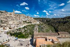 Wide panoramic cityscape view of Matera, Italy. MATERA, ITALY - AUGUST 27, 2018: Warm scenery summer day view of the amazing ancient town of the famous Sassi royalty free stock photo