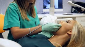 Materiał filmowy żeński cierpliwy obsiadanie w dentystach przewodniczy i żeński dentysta bierze promieniowanie rentgenowskie strz zdjęcie wideo