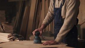 Materiał filmowy cieśla pracuje w kombinezonach Mężczyzna mleje drewno w ciesielka sklepie swobodny ruch zbiory