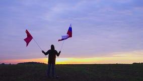 Materiał filmowy rosjanin i chińczyk zaznacza dmuchanie w wiatrze machać flaga w krajobrazie Rosjanina Chiny flaga zbiory