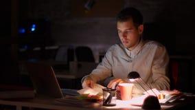 Materiał filmowy skupiający się pracujący męscy obsiadania i sprawdzać dokumenty podczas gdy trzymający papier i patrzejący ekran