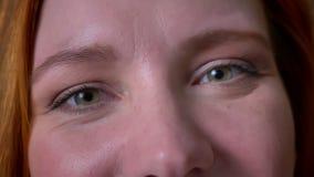 Materiał filmowy zadziwiający zieleni oczy patrzeje bezpośrednio przy kamerą i ono uśmiecha się radośnie caucasian kobieta z czer