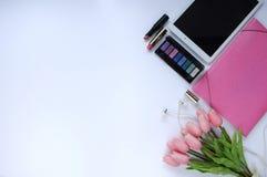 Materia de la belleza Fondo del maquillaje Aspectos del maquillaje Carpeta, tableta, flores de los tulipanes, auriculares, lápice imagen de archivo