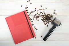 Materia del café con un portafilter, una carpeta roja y habas dispersadas en superficie de madera en la visión superior Fotos de archivo libres de regalías