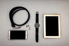 Materia del ` s de los hombres, teléfono, correa, mancuernas, relojes, imagen en el tabl Foto de archivo