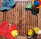 Materia del verano del niño del bebé en un fondo de madera Imagen de archivo libre de regalías