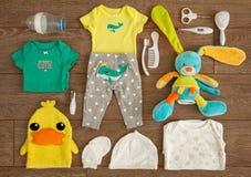 Materia esencial y accesorios del bebé recién nacido en una composición plana de la endecha en la tabla de madera Fotos de archivo libres de regalías
