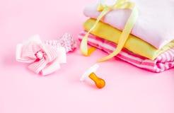 materia, ropa y pacificador recién nacidos para el bebé en fondo rosado Imagen de archivo libre de regalías
