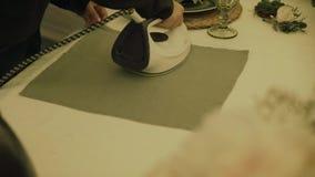 Materia textil que plancha de la mano femenina La mirada detallada en la muchacha plancha la ropa Ropa que plancha de la mujer en almacen de metraje de vídeo