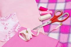Materia textil rosada y las herramientas para coser Foto de archivo