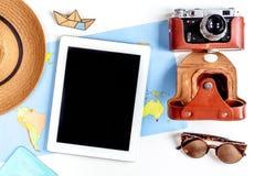 Materia turística con la cámara y mapa en la opinión superior del fondo blanco Foto de archivo
