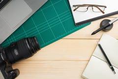 Materia y artilugios de la oficina en el escritorio de madera fotos de archivo