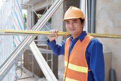 Materiais de construção levando do trabalhador fotografia de stock
