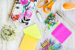 Materiais de escritório na mesa de madeira branca do trabalho com as flores Foto de Stock