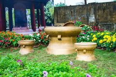 Material bronze drums on grass in vietnames. Garden flowers with with basket of flowers royalty free stock image