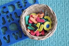 Material da escola de Montessori ajustado: ABC forma o brinquedo na cesta com placa Foto de Stock