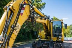 Material de construcción del cielo de Bright Yellow Blue del excavador industrial Fotos de archivo libres de regalías