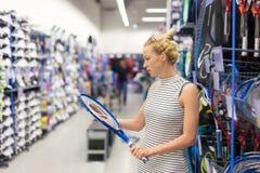 Material desportivo da compra da mulher na loja do sportswear fotos de stock