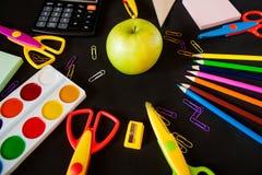 Material för skola, gemmar, blyertspennor, färger, scisor och anteckningsbok Royaltyfri Foto