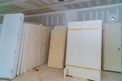 Material für Reparaturen in einer Wohnung ist im Bau und gestaltet, vorher umbauen um und Erneuerungstür für ein neues Haus stockbild
