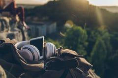 Material: Telefon, Kopfhörer, Rucksack Auf der Spitze des Berges Stockfotos
