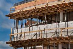 Material till byggnadsställning- och betongformwork Byggnadsplats av en kontorsbyggnad Byggnationer Arkivfoto