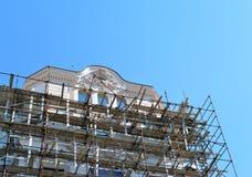 Material till byggnadsställning runt om en byggnad som renoverar fasaden royaltyfria foton