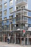 Material till byggnadsställningbyggmästare monterar ett material till byggnadsställning framme av ett blått hus Arkivfoton