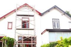 Material till byggnadsställningtornmålning reparerar det gamla huset, Nederländerna Arkivfoto