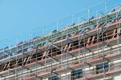 Material till byggnadsst?llning p? husfasaden som bygger under konstruktion arkivfoton
