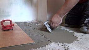 Materiale adesivo spanto mano del lavoratore del piastrellista Scivolamento della parte di sinistra video d archivio