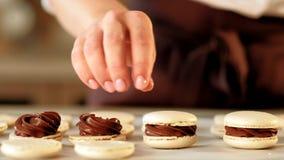 Materiale da otturazione del cioccolato dei macarons del dessert del cuoco di pasticceria video d archivio